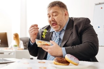 Comical chubby guy not sticking to his diet